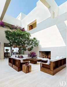 Outdoor living space with a living room set and trees of a modern luxury home